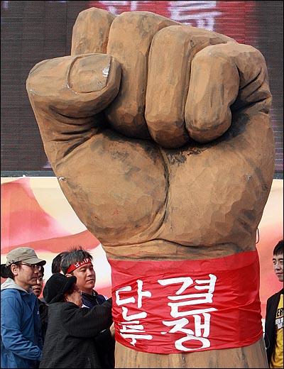 제120주년 세계 노동절인 1일 오후 서울 여의도 문화공원에서 열린 '120주년 세계노동절 기념 범국민대회'에서 전태일 어머니 이소선 여사와 김영훈 민주노총 위원장이 모형 주먹에 '단결투쟁' 띠를 두르는 상징의식을 하고 있다.