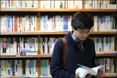책방을 둘러보고 찾는 책을 펼쳐보고 있다.