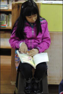 한 여자 아이가 동화책을 집중해 보고 있다.