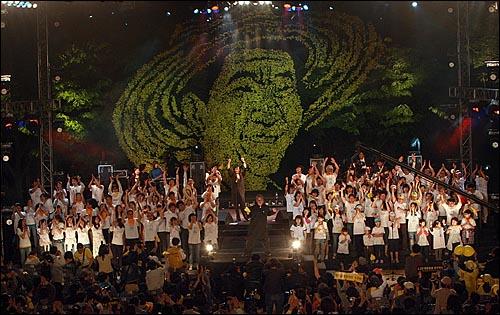 8일 밤 서울 구로구 성공회대학교 운동장에서 열린 '고 노무현 전 대통령 서거 1주기 추모 콘서트-파워 투 더 피플(Power to the People)'에서 시민 합창단이 노래 `파워 투 더 피플(Power to the People)을 합창하고 있다.