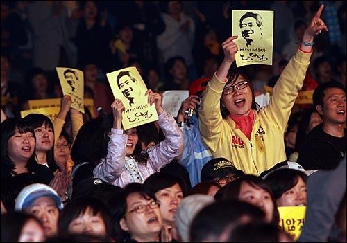 8일 밤 서울 구로구 성공회대학교 운동장에서 열린 '고 노무현 전 대통령 서거 1주기 추모 콘서트-파워 투 더 피플(Power to the People)'에서 한 시민들이 노무현 대통령의 얼굴이 그려진 손피켓을 들어보이며 공연을 즐기고 있다.