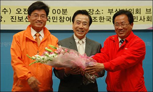 12일 부산시의회 브리핑룸에서 부산시장 야권단일후보로 선정된 김정길 후보가 꽃다발을 받고 민병렬, 김석준 후보와 환하게 웃고 있다.