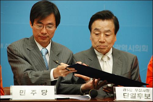 12일 부산시의회 브리핑룸에서 열린 기자회견에서 민주당 조경태 의원과 부산시장 야권단일후보인 김정길 후보가 '희망 10대 과제'에 서명하고 있다.