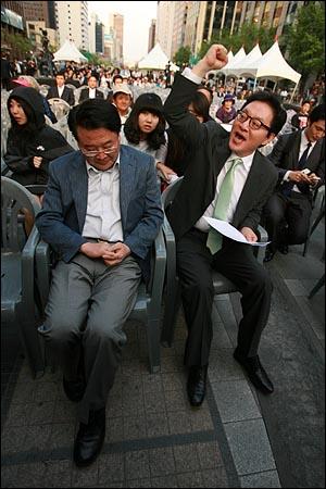 법원 판결을 무시하고 전교조 등 교원단체 명단을 공개해서 강제이행금을 물게 된 한나라당 조전혁 의원이 13일 오후 서울 청계광장에서 자신을 돕기 위해 개최되는 콘서트를 앞두고 의자에 앉자, 정두언 의원이 '조전혁 화이팅'을 외치고 있다.