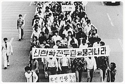 """""""신현확 전두환은 물러가라""""는 캐치프레이즈는 전국 모든 대학교의 요구사항이었다. 5.18 광주항쟁이 일어나기 직전 대학교수가 앞서고 대학생들이 뒤따르는 평화시위 모습이다"""