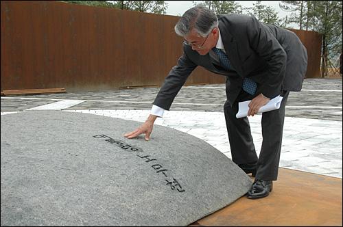 문재인 (재)노무현재단 상임이사가 19일 봉하마을 고 노무현 대통령 묘역에서 추가공사를 완공한 뒤 설명하면서 봉분 역할을 하고 있는 너럭바위를 손으로 만져보고 있다.