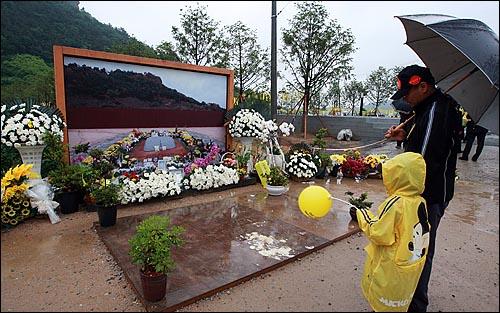 고 노무현 전 대통령 서거 1주기를 맞은 23일 오전 경남 김해시 봉하마을 노 전 대통령 묘역을 찾은 추모객들이 고인의 넋을 기리고 있다.