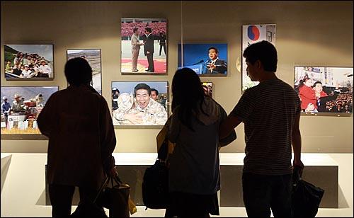 고 노무현 전 대통령 서거 1주기를 맞은 23일 오전 경남 김해시 봉하마을 노 전 대통령 묘역 앞에 마련된 '노무현 대통령 추모의 집'에서 추모객들이 노 전 대통령의 사진들을 둘러보고 있다.