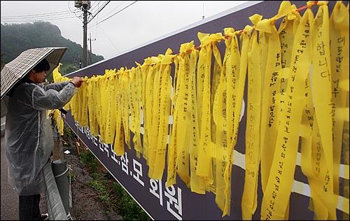 고 노무현 전 대통령 서거 1주기를 맞은 23일 오전 경남 김해시 봉하마을 노 전 대통령 묘역을 찾은 추모객이 노란 리본에 추모의 글귀를 적어 매달고 있다.