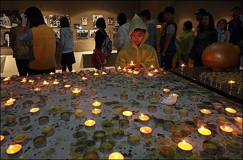 고 노무현 전 대통령 서거 1주기를 맞은 23일 오전 경남 김해시 봉하마을 노 전 대통령 묘역 앞에 마련된 '노무현 대통령 추모의 집'에서 한 어린이가 고인의 넋을 기리며 촛불에 불을 밝히고 있다.