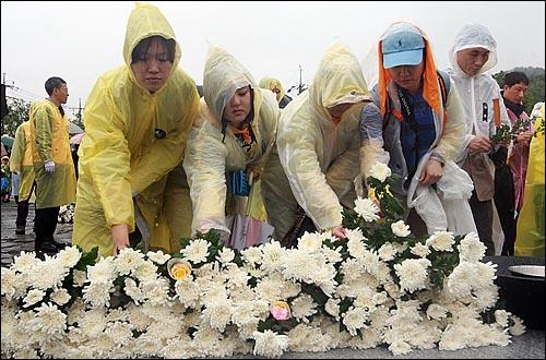 고 노무현 전 대통령 서거 1주기를 맞은 23일 오후 경남 김해시 봉하마을에서 추모객들이 추모식을 마친 뒤 묘역을 찾아 헌화를 하고 있다.