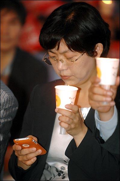 """3일 저녁 서울광장에서 개최된 """"4대강 사업 중단을 위한 범국민대회""""에 참석한 민노당 이정희 의원이 스마트폰을 이용해 트위터에 현장 상황을 올리고 있다."""
