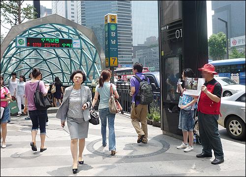 5일 오후 강남역 7번 출구 앞에서 이철민(가명, 55)씨가 도우미와 함께 노숙인의 자립을 위한 잡지 '빅이슈 코리아'를 판매하고 있다.