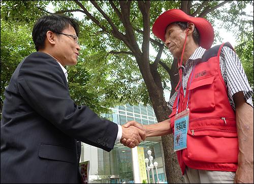 5일 오전 광화문역 6번 출구 앞에서 노숙인의 자립을 위한 잡지 '빅이슈 코리아'를 판매하는 권일혁(58)씨가 첫 구입 손님과 인사를 나누고 있다.