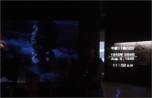 나가사키 시립 원폭자료관에 전시된 영상자료. 영상에서는 원자폭탄이 터지는 장면이 흘러나오고, 그 옆에서 원자폭탄이 떨어진 시간이 표시되어 있다.