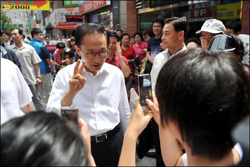 이명박 대통령이 22일 강서구 화곡동 까치산시장을 방문해 시민들의 사진 촬영에 응하고 있다.