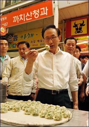이명박 대통령이 22일 강서구 화곡동 까치산시장을 방문해 분식집에서 만두를 맛보고 있다.