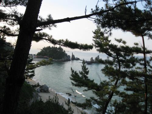 야트막한 산 위에서 내려다본 촛대바위. 바위 바로 왼쪽으로 보이는 나무들 사이에 해암정이 있다.