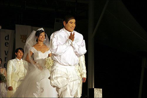 생전의 앙드레 김 세계적 패션디자이너 앙드레 김이 '2006 세계평화축전'에서 평화를 디자인한 패션쇼를 마치고 주역 모델인 박다안 등과 함께 관객들에게 인사하고 있다.