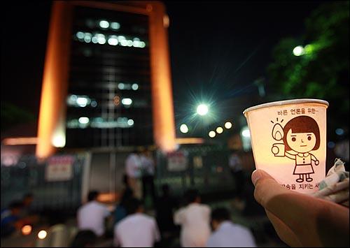 김재철 사장이 'PD수첩-4대강 수심 6m의 비밀' 편을 방송보류 결정을 내린 가운데 17일 밤 서울 여의도 MBC 사옥 앞에 모인 시민들이 방송 불방사태에 항의하며 촛불을 들어보이고 있다.