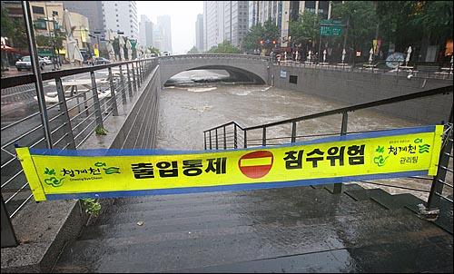 민족 최대 명절인 추석 연휴 첫날인 21일 오후 서울·경기 지역에 시간당 최대 100mm의 폭우가 쏟아진 가운데, 종로구 청계천 산책로가 물에 잠겨 시민들의 출입이 통제되고 있다.