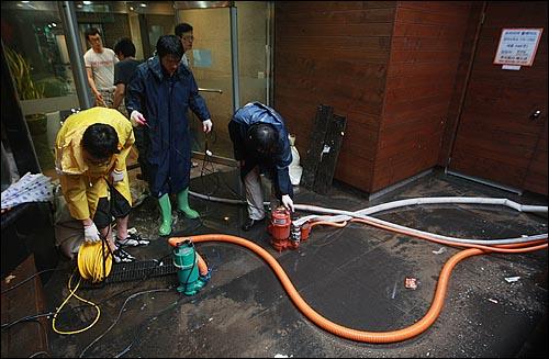 민족 최대 명절인 추석 연휴 첫날인 21일 오후 서울·경기 지역에 시간당 최대 100mm의 폭우가 쏟아진 가운데, 종로구 청계천 인근 한 지하식당에 물이 들어차자 직원들이 배수펌프를 이용해 물을 빼내고 있다.