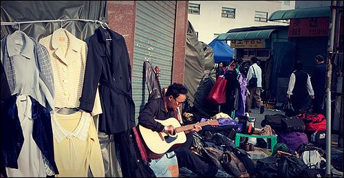 기타 연주하는 사장님 이 아저씨는 옷을 파는 분인데 늘 이렇게 앉아서 기타를 연주하고 있다.  가만히 보니 오른손이 화상을 입었는지 온전하지 않은데 기타에 대한 열정은 대단하다.