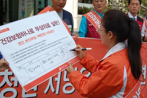 건강보험 하나로 입법청원운동 선포  김혜영 민노당 충남도당위원장이 입법청원 서명서에 서명을 하는 포퍼먼스를 하고 있다.