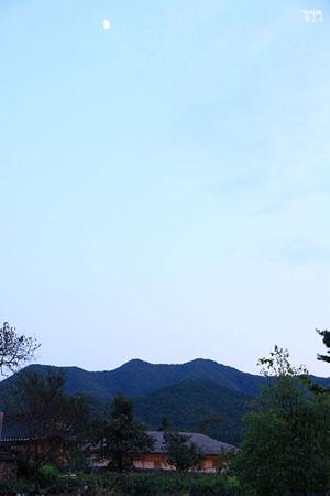 초가지붕 위로 높이 솟은 반달