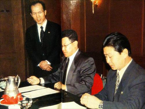 97년 2월 베이징 캠핀스키 호텔에서 광고기획사 '아자'의 박기영 대표와 금강산관광총회사 박종삼 총사장이 북한에서의 광고촬영 계약서에 서명하고 있다. 서 있는 사람이 '아자'의 전무로 위장한 흑금성 공작원 박채서씨.
