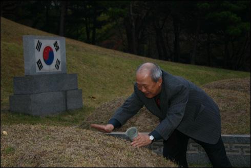 기자가 뤼순공동묘지에서 취토해 온 흙을 효창원 안중근 의사 무덤 봉분에 덮고 있다.