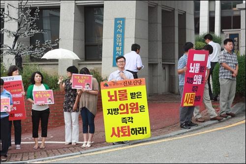 여수시민협 김태성 사무국장(가운데)이 여수시의회 앞에서 뇌물받은 지방 의원은 사퇴하라!고 쓰인 노란 피켓을 들고 피켓팅을 하고 있다.