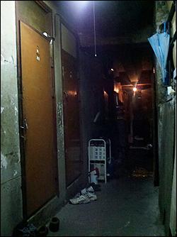 어두컴컴한 쪽방촌의 복도, 한층에 12개의 방이 오밀조밀하게 붙어있다.