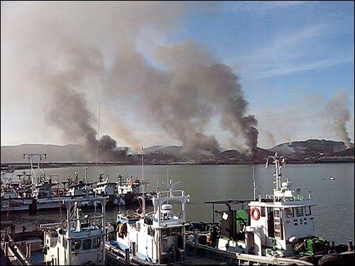 23일 오후 북한이 발사한 포탄이 연평도에 떨어져 폭발하면서 섬 곳곳에서 시커면 연기가 피어오르고 있다. 연평도를 방문한 한 시민이 제공한 화면.