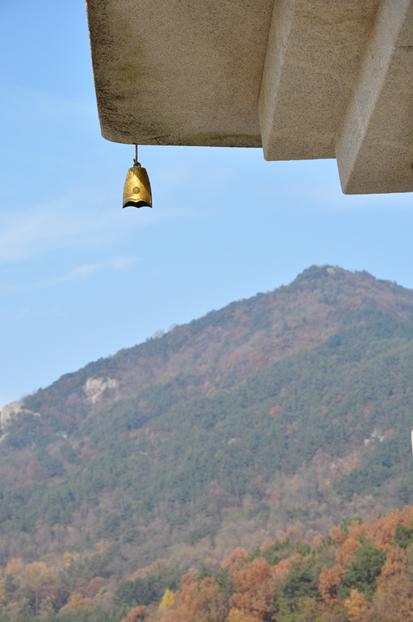 미륵탑 끝에 달린 풍탁 뒤로 백제의 숨결을 담고 있는 미륵산의 모습이 펼쳐져 있다.
