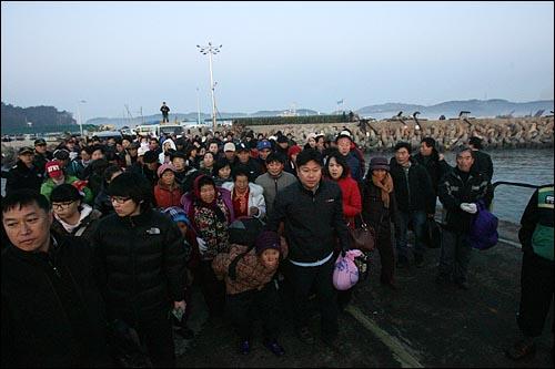 북한군의 포격을 받은 인천 옹진군 연평도에서 24일 새벽 주민들이 섬을 떠나기 위해 짐보따리를 들고 부두로 몰려들고 있다.