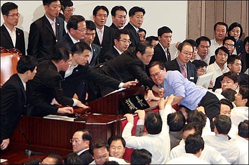 8일 오후 서울 여의도 국회 본회의장에서 정의화 국회부의장이 2011년 예산안을 강행처리를 시도하자, 홍영표 민주당 의원이 예산안 표결 처리를 막기 위해 의장석으로 뛰어오르고 있다.