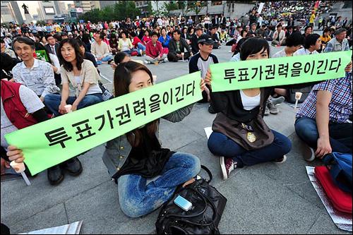 '6.2 지방선거' 를 하루 앞둔 지난 6월 1일, 서울 광화문 광장에서 시민들이 '투표가 권력을 이긴다' 라고 쓰인 선전물을 펼쳐 보이고 있다.