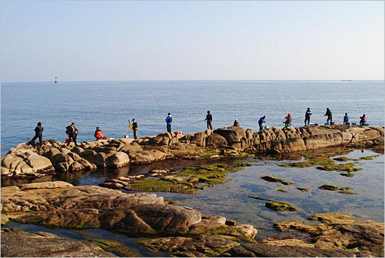 갯바위에 올라서 낚시를 즐기는 사람들