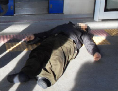 전철안에서 넘어져 정신을 잃은 남자가 밖에서 누워있다.