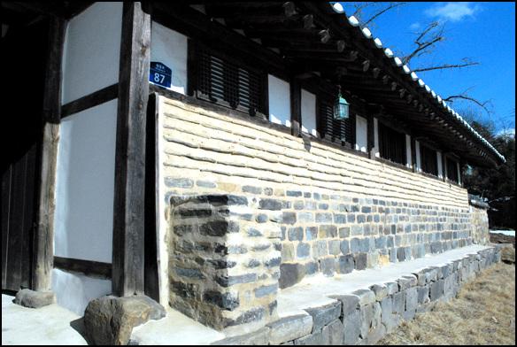 대문채 10칸의 ㅡ 자형으로 구성이 된 대문채의 우측. 대문 옆에 담장에 붙은 낮은 굴뚝이 재미있다.