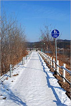 '물안개 피어나는 야생화 산책로'라고 이름이 붙은 길. 자전거 겸용 표지판이 세워져 있다. 눈이 덮여 있어 조심스럽게 지나가야 한다.