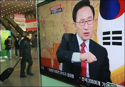 1일 오전 서울역 대합실에 설치된 TV 모니터를 통해 이명박 대통령의 '2011 신년방송좌담회-대통령과의 대화'가 생중계 방송되고 있는 가운데, 한 시민이 TV 모니터 옆을 지나가고 있다.