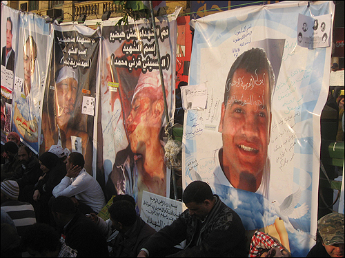 11일(현지 시각) 오후 이집트 수도 카이로의 타흐리르 광장에 모인 시민들이 '무바라크 퇴진'을 요구하다 희생된 이들의 사진 앞에 앉아 있다.