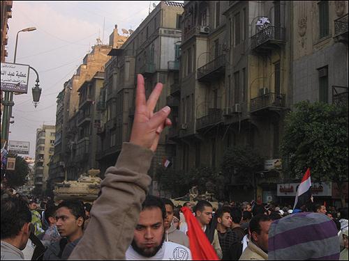 11일(현지 시각) 오후 이집트 수도 카이로의 타흐리르 광장에 시민들이 '무바라크 퇴진'을 요구하고 있는 가운데, 한 여성이 카메라 앞에서 승리의 브이(v)자를 그려 보이고 있다. 그 너머로 광장을 둘러싼 탱크가 보인다.