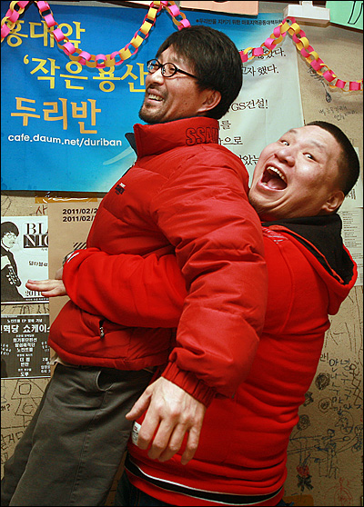 프로레슬링 선수 겸 격투기 해설자 김남훈이 강제철거에 반대하며 420일째 농성을 하고 있는 칼국수집 '두리반'을 방문해 유채림 사장을 안아주며 위로와 용기를 북돋아 주고 있다.