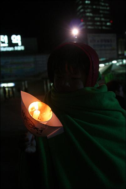 '평화'와 '반전' 촛불 반전평화 촛불문화제에 참가한 한 어린이가 배모양의 종이에 '반전', '평화'가 씌여진 촛불을 들고 있다.