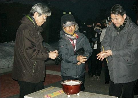 향을 피우는 박영희 시인(우측)과 인솔자 김두현(가운데), 김종해 총경리(좌측)