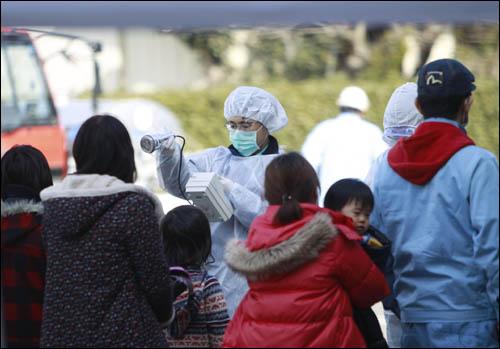 13일 일본 후쿠시마현 고리야마시에서 제1원자력발전소 폭발현장 인근서 대피한 이들이 방사선 노출 여부를 검사받고 있다.