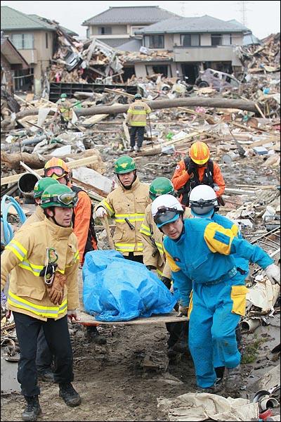 시신 옮기는 중앙119구조단원들 일본 동북지방에 진도 9의 강진이 발생한지 나흘이 지난 15일 오전 119중앙구조단원들이 지진으로 인한 쓰나미 피해지역인 일본 미야기현 센다이시 미야기노구 가모지구에서 센다이 경찰과 함께 실종자 시신을 옮기고 있다.